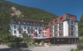 Hotel du Nord Bernese Oberland exterior white building with red panel and red window frames wooded hill