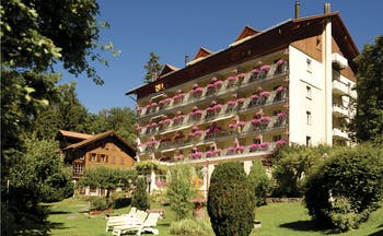 Hotel Wengenerhof exterior, hotel building in traditonal Swiss style, gardens with lawn andd shrubbery, sun loungers