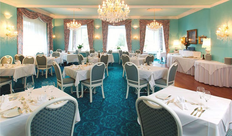 Hotel Wengenerhof restaurant, tables and chairs, traditional decor, chandaliers, blue carpet