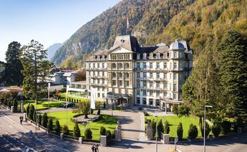Lindner Grand Hotel Beau Rivage Bernese Oberland exterior building with balconies and Swiss flag wooded hill