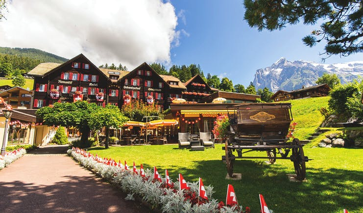 Romantik Hotel Schweizerhof exterior, hotel building in traditional swiss style, grounds and lawn, mountains in background