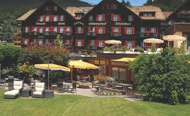Romantik Hotel Schweizerhof grounds, hotel building, lawns, patio, sun loungers, umbrellas