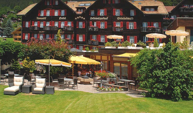 Romantik Hotel Schweizerhof grounds, hotel building, lawns, patio, sun loungers, umbrellas