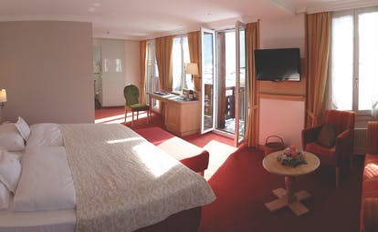 Romantik Hotel Schweizerhof junior suite, double bed, lounge area, private balcony, traditional decor