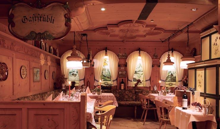 Romantik Hotel Schweizerhof restaurant, traditional Swiss decor, tables and chairs