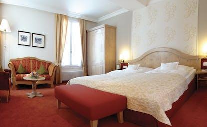 Romantik Hotel Schweizerhof suite, double bed, sofa, traditional colourful decor