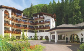 Arabella Hotel exterior, hotel building in traditonal Swiss style, hotel entrance, large fir trees in background