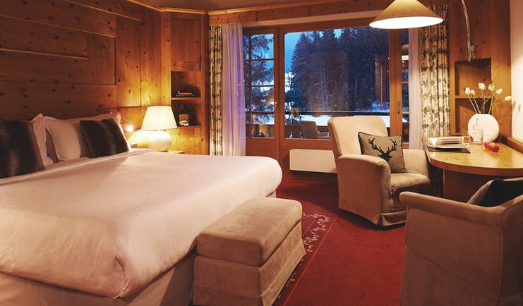 Arabella Hotel superior room, bed, armchairs, traditional Swiss decor, balcony out onto the snow