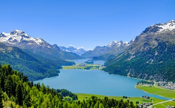 Sils and Silvaplana Lakes, surrounded by lush fields, small villages, evergreen woods, snowcapped mountains