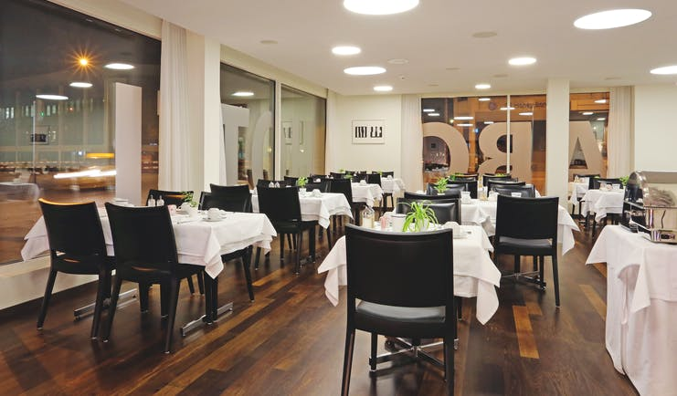Hotel ABC dining room with multiple tables set out with black chairs in a white room with wooden floors