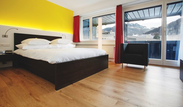 King bedroom in the hotel ABC with a yellow wall, doors that open up onto a balcony and a large black and white bed