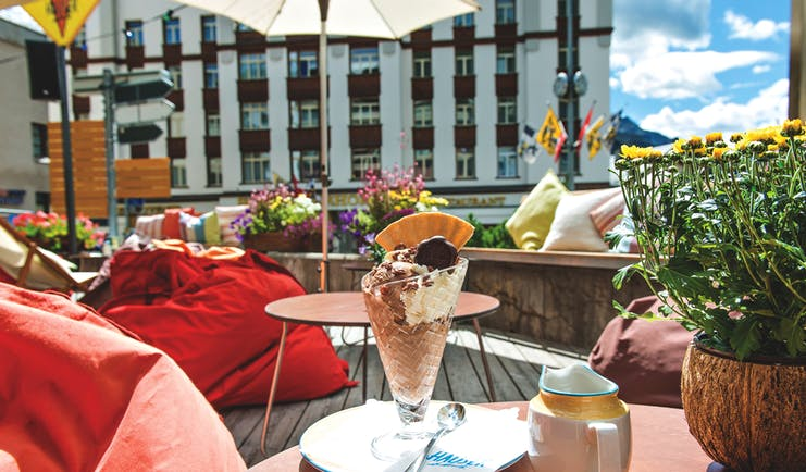 Hotel Hauser Grisons and the Engadine outdoor terrace bean bags and flowers a table with an ice cream sundae