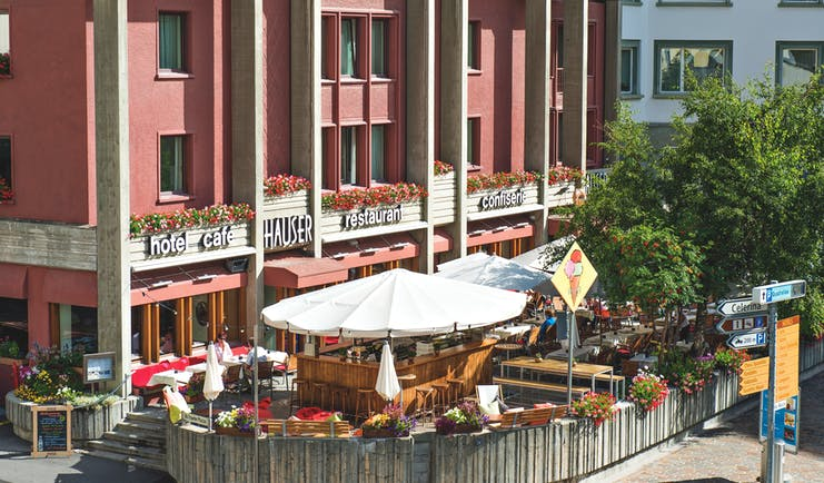 Hotel Hauser Grisons and the Engadine terrace area with umbrellas