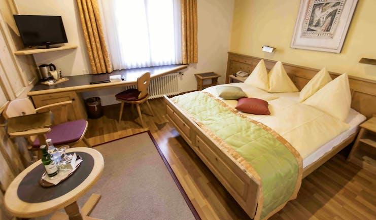Romantik Hotel Stern guestroom, double bed, desk, bright traditional decor