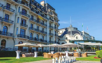 Beau Rivage Palace Hotel Lake Geneva exterior large building with balconies a conservatory and outdoor terrace