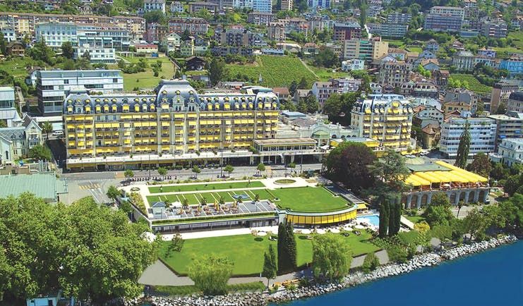 Fairmont le Montreux Palace Lake Geneva aerial of large yellow building lawns and swimming pool near a lake
