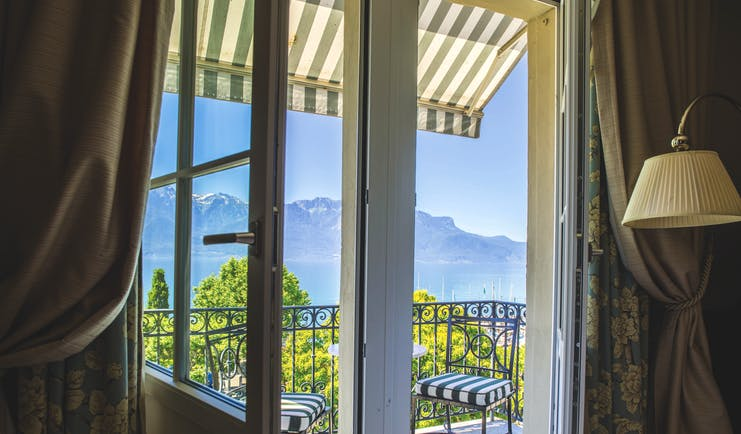 View from inside a room at Grand Hotel du Lac looking out past the balcony, onto blue skies and the mountains