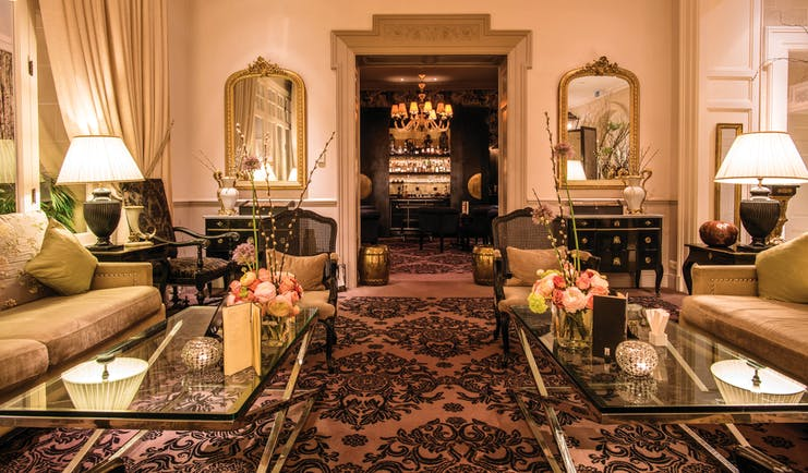 Grand Hotel du Lac lounge area with large archway leading to a bar with a large chandelier, glass tables, gold rimmed mirrors and floral sofas