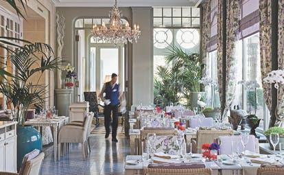 Grand Hotel du Lac Restaurant, La Veranda, a bright room with big windows, drawn floral curtains, a chandeleir, and neatly set tables and chairs