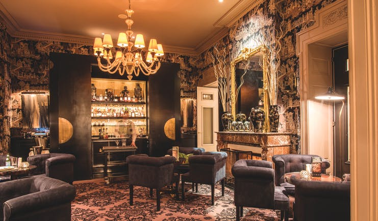 Grand Hotel du Lac bar, with a cabinet of drinks, a large chandelier, a fireplace and navy armchairs