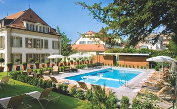 Hotel Angleterre et Residence Lake Geneva exterior pool with topiary potted trees