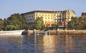 Hotel exterior with full view of large hotel building and lake in front