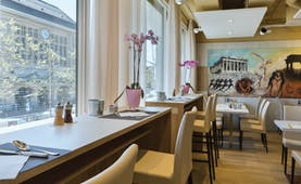 Hotel Continental breakfast room, bright decor, tables and chairs, large windows, ancient greek artwork
