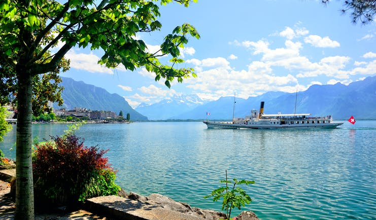 Riviera at Montreux, Lake Geneva, large lake boat, town on left side, mountains in background