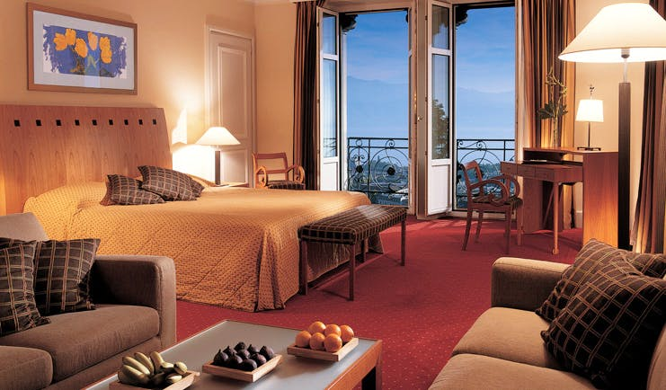 Lausanne Palace Switzerland deluxe bedroom lounge area with sofas and balcony