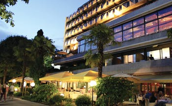 Royal Plaza Montreux exterior, hotel building, contemporary architecture, dining terrace under large umbrellas, trees