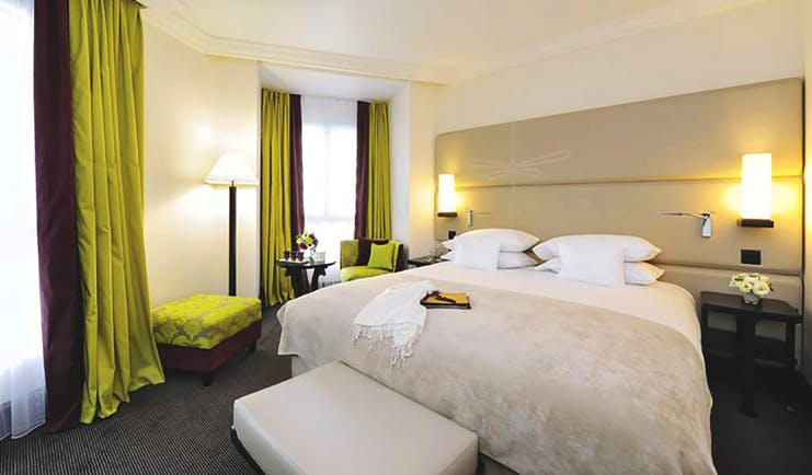 Tiffany Hotel deluxe room, large bed, brightly coloured curtains, modern decor