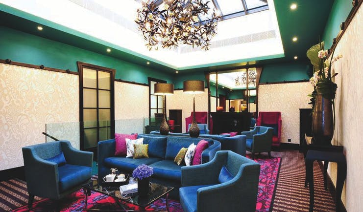 Tiffany Hotel lobby, velvet sofas and chairs, glass ceiling, bright decor