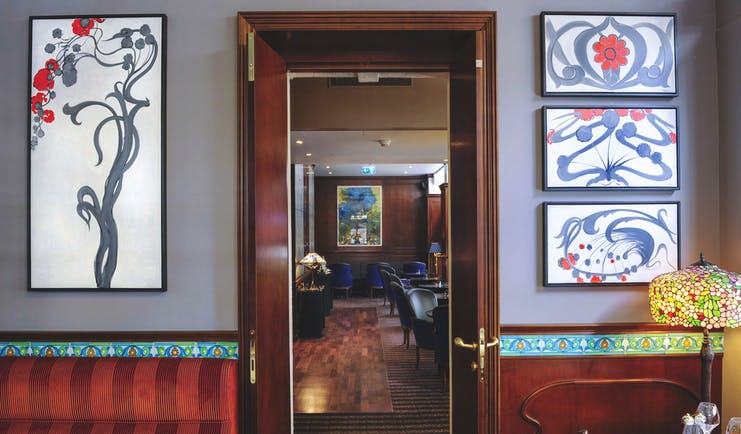Tiffany Hotel restaurant view through doorway, low blue velvet chairs, wooden details, paintings on wall