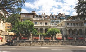 Villa Toscane exterior, grand hotel building in Swiss Italian style, turrets and windows, trees