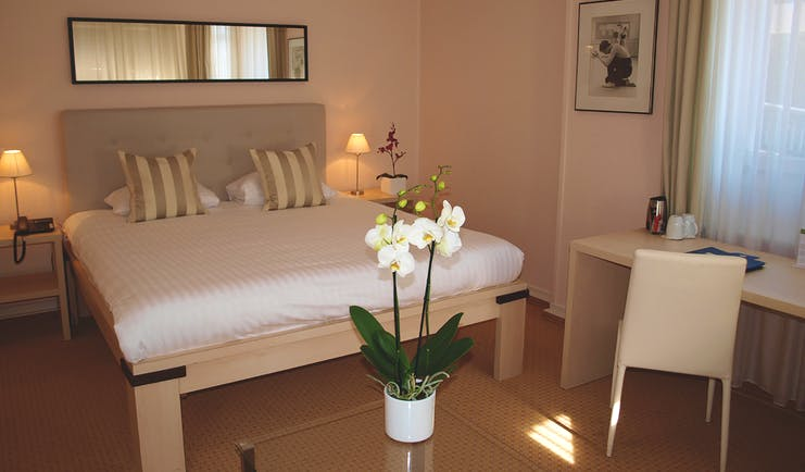 Villa Toscane superior guestroom, double bed, desk, white elegant decor