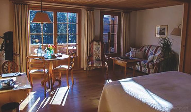 Hotel Alpenrose suite, double bed, sofa, doors leading to balcony, alpine style decor