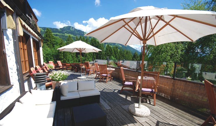 Hotel Alpenrose terrace, dining tables and chairs, umbrellas, sofa, view of mountains