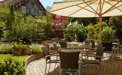 Gstaaderhof chairs and tables with umbrellas in garden with old chalet behind