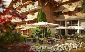 Gstaaderhof wooden chalet hotel with balconies and umbrellas in garden