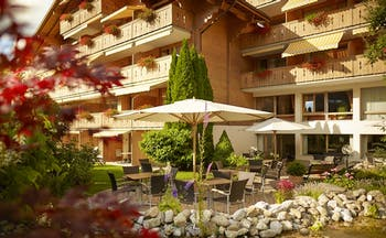 Gstaaderhof wooden chalet hotel with balconies and umbrellas in garden