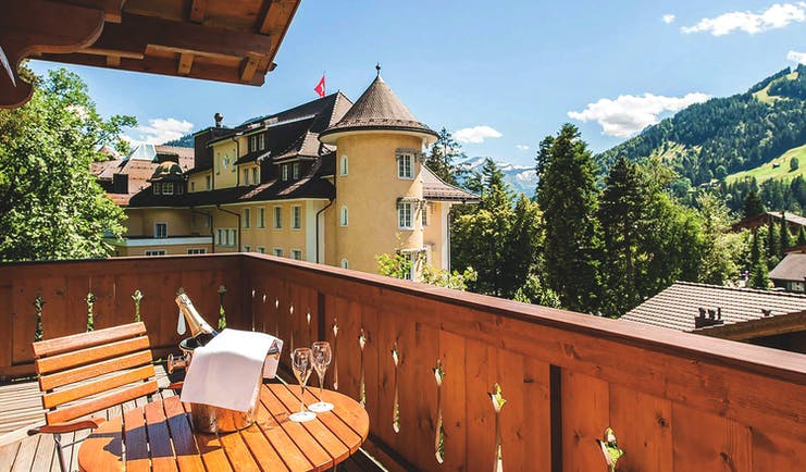 Le Grand Bellevue balcony, outdoor seats with champagne bucket, views of mountains and traditonal Swiss architecture
