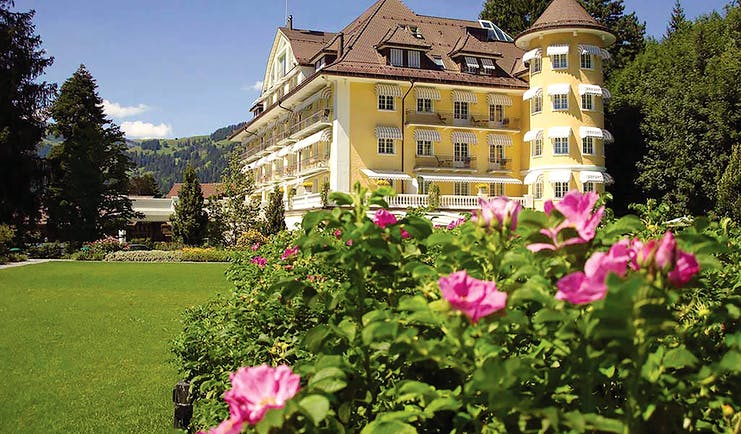 Le Grand Bellevue exterior, yellow building with white windows, turrets, traditional Swiss architecture