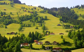 Alpine valley, meadows, and village, Alpine style houses dotting the hillside