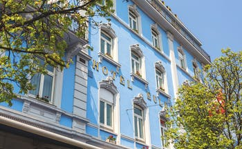 Blue hotel building with white window surrounds Hotel Euler Basel