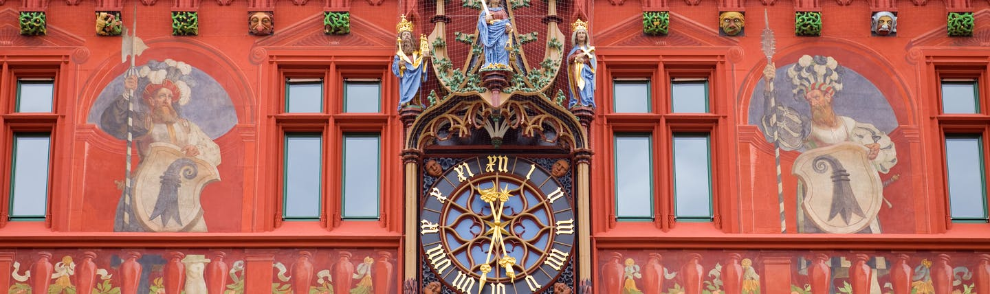 Facade of the Red Town Hall in Basel, clock, intricate painting of guards, statues of Jesus