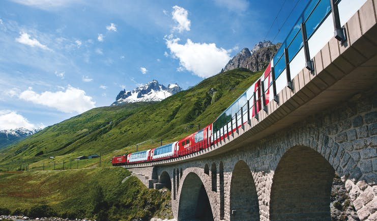 Red Bernina Express train on bridge near Hospental