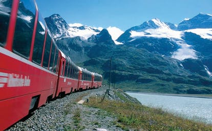 Side of red train passing lake with snow on mountains