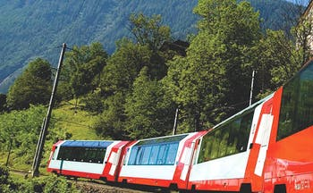 Red train with Glacier Express on side in mountains
