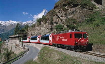 Red train engine pulling red and white coaches of the Glacier Express in summer mountains