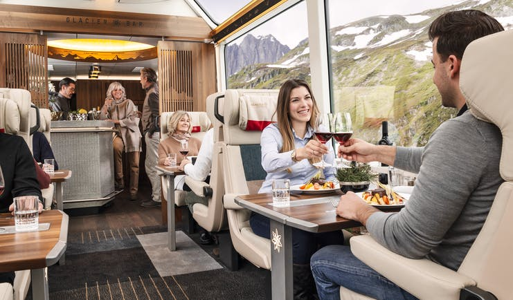 Couple in panoramic rail carriage at table dining with mountains outside